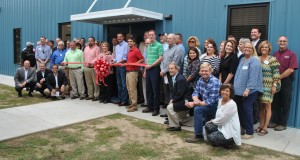 Becky Crissman/Cordele Dispatch Helena Chemical executives, chamber members, and local officials celebrated the plant's ribbon cutting of a new employee break room and shower facility.
