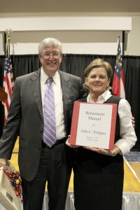 After reading a poem for Pridgen, secretary Cheri Slade presented him with a retirement manual to assist him as he adapts to life without a secretary keeping his schedule.
