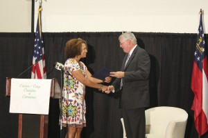 Becky Crissman/Cordele Dispatch A representative from Congressman Sanford Bishop's office presents Pridgen with a letter from Bishop honoring his achievements.