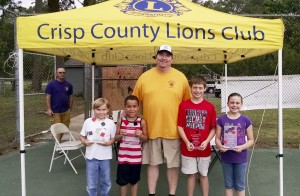 Winners of the youth division of the Cornole Tournament (l-r) 1st place Shelton Dickerson and Caden Lofton, Crisp Lions President Gary Cross, and 2nd place winners Ryan and Riley Reed.